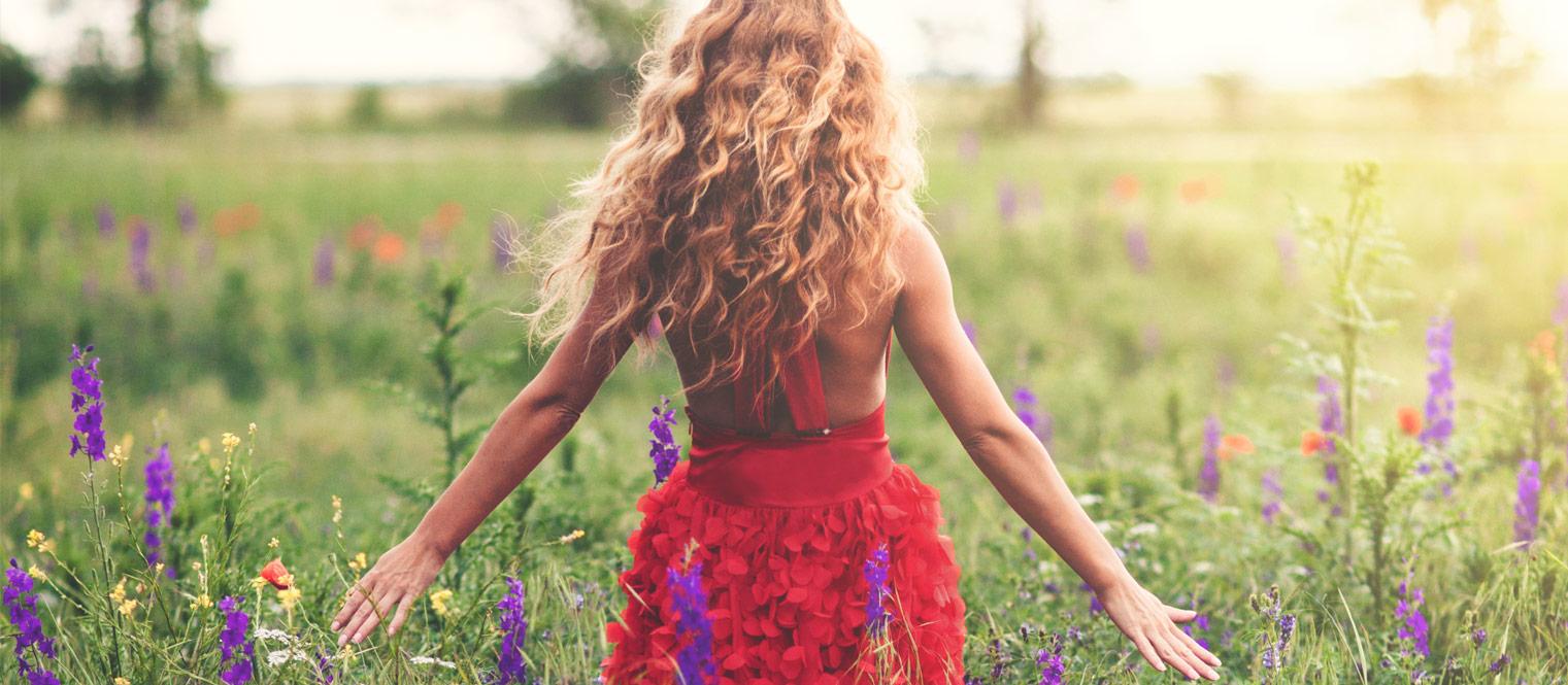 Kuukuppia käyttävä nainen kukkaniityllä