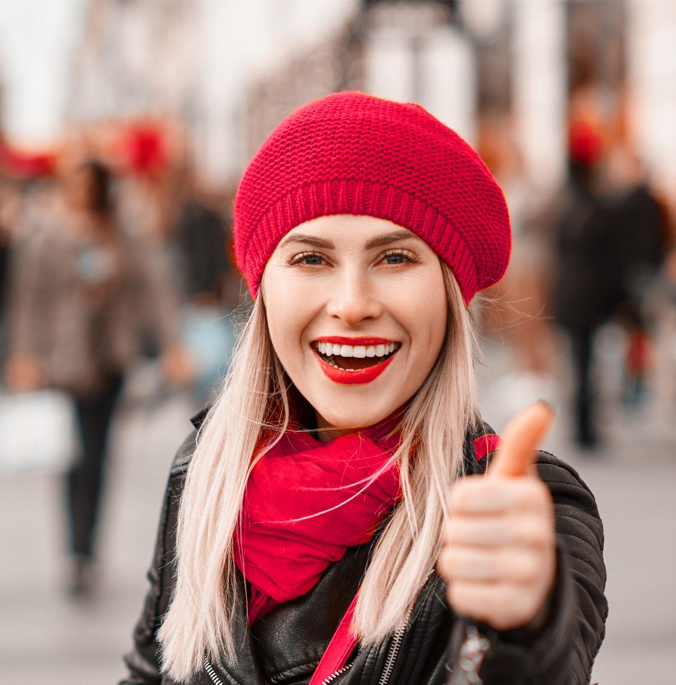 Kuukuppia käyttävä nainen hymyilee peukalo pystyssä