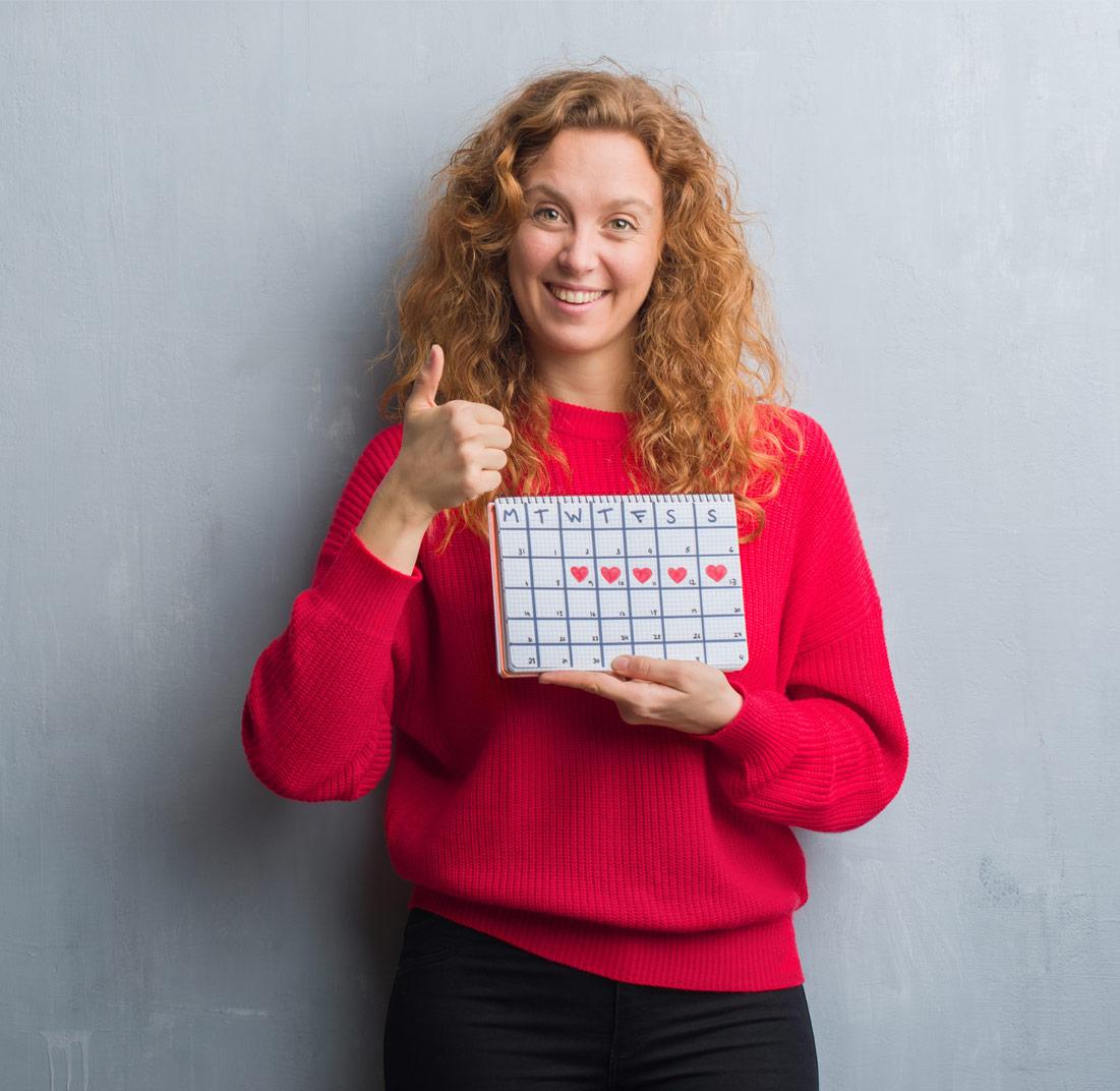 Kuukuppia käyttävä nainen pitelee kädessään kalenteria