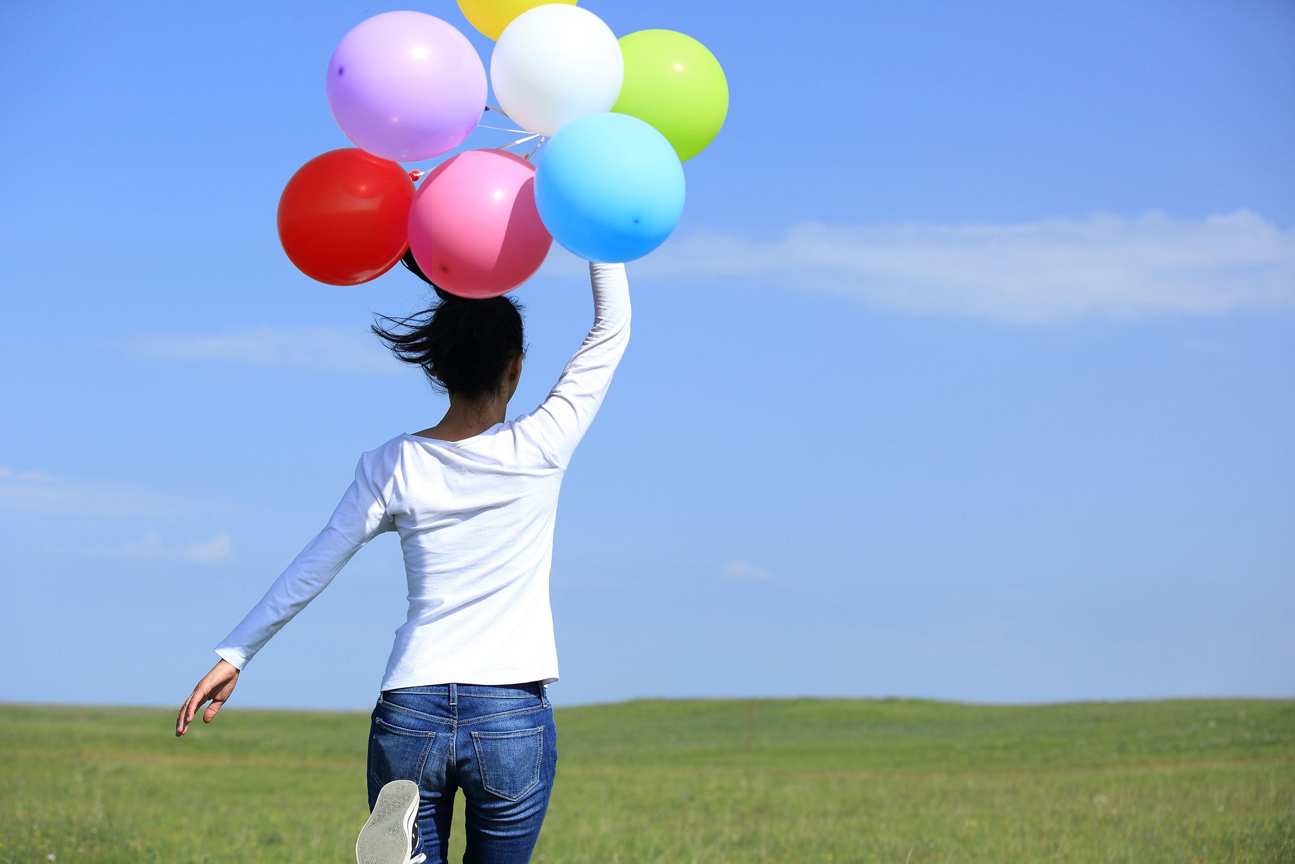 Kuukupin käyttäjänainen juoksee ilmapallojen kanssa